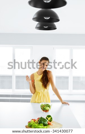Healthy Food. Close Up Of Happy Smiling Girl Eating Vegetable Vegetarian Salad In Modern Kitchen. Healthy Eating And Lifestyle. Health, Beauty, Diet Concept. Nutrition. - stock photo