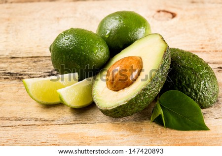 healthy food concept - avocado and lime slices on wooden background - stock photo