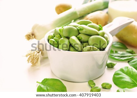 Healthy food concept. Ceramic dipper of fava beans with ingredients for cream soup on white table. - stock photo