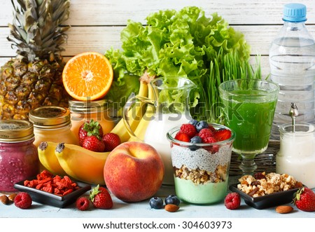 Healthy food concept. Fresh fruit and berries, granola and yogurt, smoothies and green wheat grass juice, almond milk and goji. - stock photo
