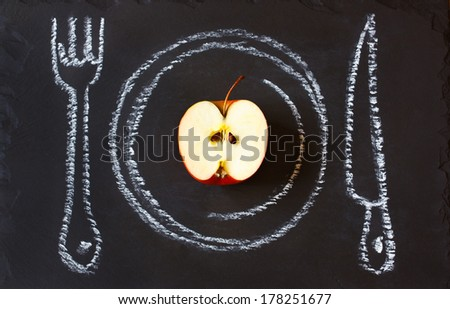 Healthy food concept. Fresh organic apple on a chalk painted plate. - stock photo