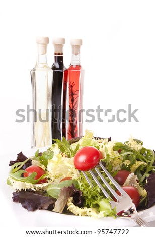 Healthy food concept - Tomatoes and green salad with styled aromatic vinegar bottle on background - stock photo