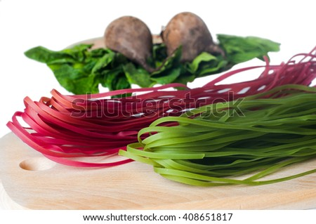 Healthy food concept: two different kinds of colorful raw italian pasta and its natural vegetable dyes (spinach, paprika)  on wooden desk, over light background. Shot in shallow depth of field - stock photo