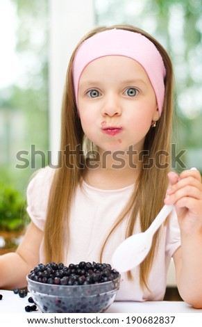 Healthy food. Cute little girl eating blueberries - stock photo
