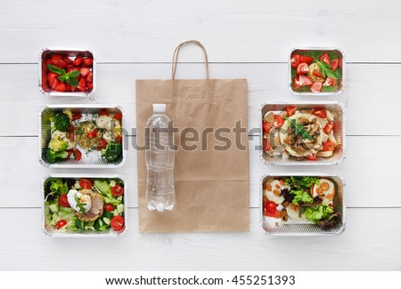 Healthy food delivery, daily meals and snacks. Diet nutrition, vegetables, meat, water bottle and fruits in foil boxes and brown paper package. Top view, flat lay at white wood with copy space - stock photo