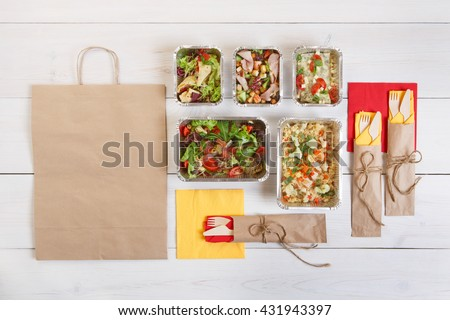 Healthy food delivery. Take away of natural organic low carb. Eat right concept, healthy food, fitness nutrition take away in aluminium boxes, cutlery and package, top view, flat lay at white wood - stock photo