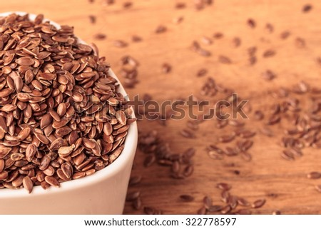 Healthy food diet. Brown flax seeds linseed in white bowl on wooden table - stock photo