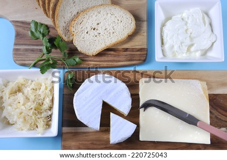 Healthy Food Diet: Probiotic Food including sour dough bread, sauerkraut, yogurt, Parmigiano-Reggiano and Camembert cheeses on wood chopping boards against a blue background. - stock photo