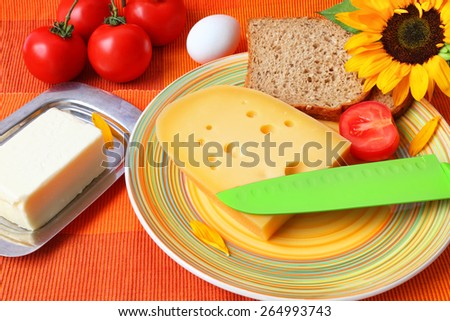 Healthy food for breakfast served on a bright color napkin with a sunflower - Cheese, butter, boiled eggs, sliced rye bread with bran and fresh tomatoes  - stock photo