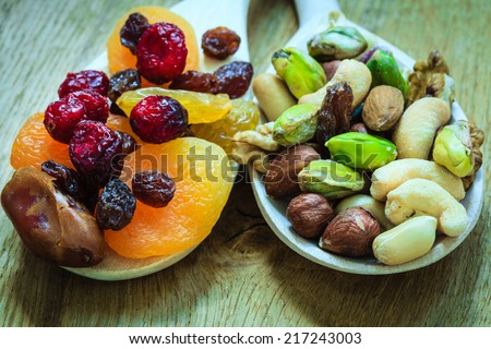Healthy food organic nutrition. Closeup different varieties mix of dried fruits and nuts on wooden spoons. - stock photo