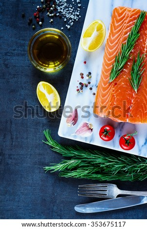 Healthy food - raw salmon fillet, preparation with fresh seasoning, olive oil and lemon on marble cutting board. Background layout with free text space. Diet or cooking concept. - stock photo