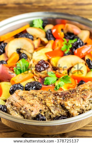 Healthy food, stewed pork meat with various colorful vegetables in pan on wooden background, selective focus - stock photo
