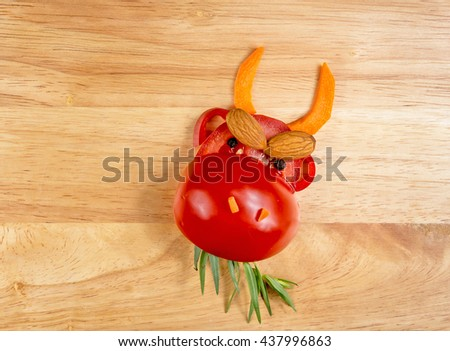 Healthy food. The figure of a cow made of vegetables and fruits on wooden board - stock photo