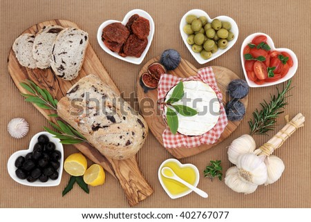 Healthy fresh food with olive bread and olives, camembert, fresh and sun dried tomatoes, herbs, garlic, oil and figs. - stock photo