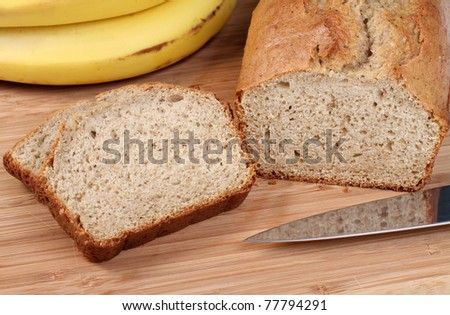 Healthy, fresh from the oven banana bread on a cutting board.  Two slices to the side with bananas in the background. - stock photo