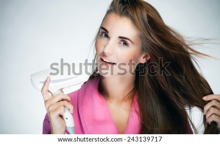 Healthy fresh girl drying her long hair with blow dryer - stock photo