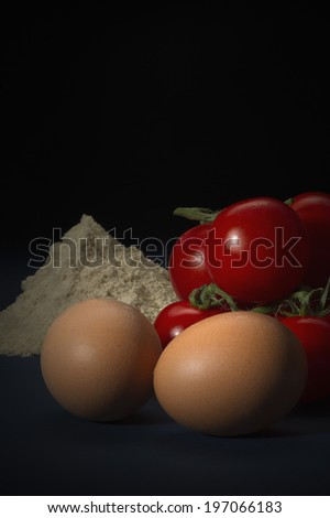 Healthy fresh ingredients including brown free range eggs, flour and ripe cherry tomatoes in a country kitchen ready to be used in cooking, vertical format on a dark background with copyspace - stock photo