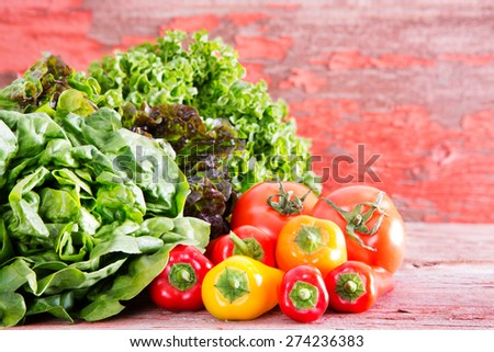 Healthy fresh salad ingredients at a farm market with assorted lettuce varieties displayed on rustic wooden boards with ripe red tomatoes and sweet bell peppers, with copy space - stock photo