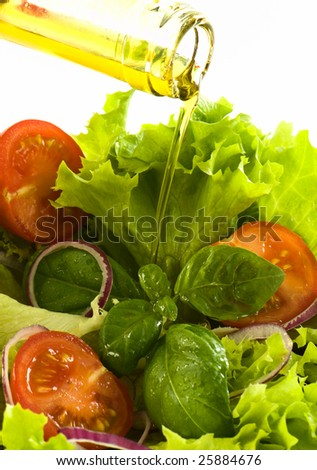 healthy fresh salad isolated on white background. Olive oil being poured on the salad. Healthy lifestyle. - stock photo