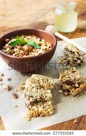 Healthy fruit and nuts granola bars, a jar of honey and a bowl of granola on vintage wooden background - stock photo