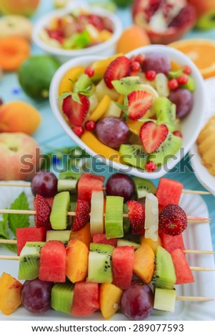 Healthy fruit salad, fruit skewer, strawberry tart - summer party - stock photo