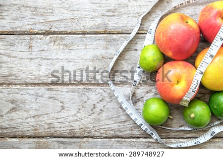 Healthy Fruit with measuring tape on wooden top , for lose weight ,Diet , still life background, Healthy lifestyle concept - stock photo