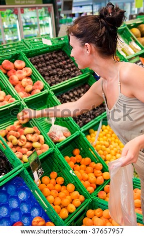 Healthy fruits food buying woman with apples in supermarket - stock photo
