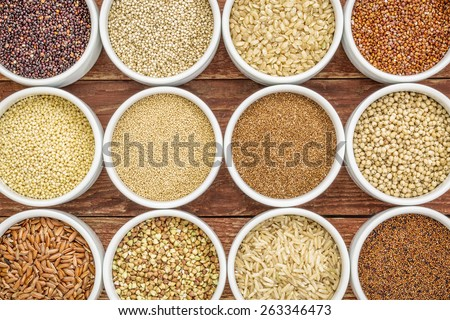healthy, gluten free grains abstract (quinoa, brown rice, millet, amaranth, teff, buckwheat, sorghum), top view of small round bowls against rustic wood - stock photo