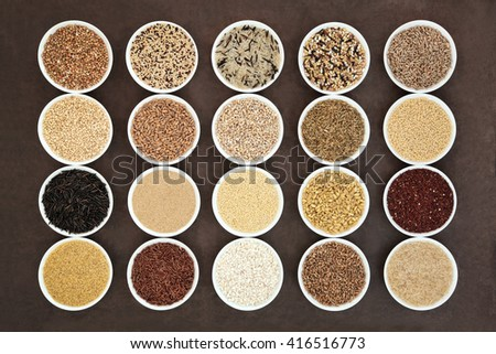 Healthy grain food selection in round porcelain bowls over lokta paper background. - stock photo