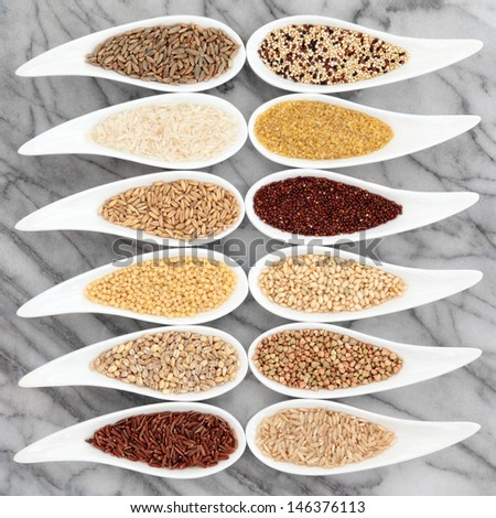 Healthy grain food selection in white china porcelain dishes over marble background. - stock photo