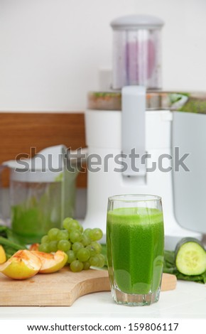 Healthy green juice poured into a glass - stock photo