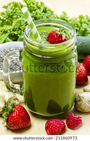Healthy green juice smoothie surrounded by whole fruits, vegetables and chia seeds with fresh strawberry garnish and green swirl straw - stock photo
