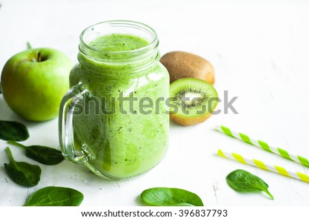 Healthy green smoothie and ingredients on white - spinach, apple and kiwi. Superfood, detox and  healthy food. - stock photo