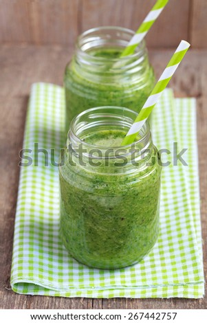 Healthy green smoothie made from spinach, kiwi, bananas and oranges in a jar with green straws on a wooden table, selective focus - stock photo