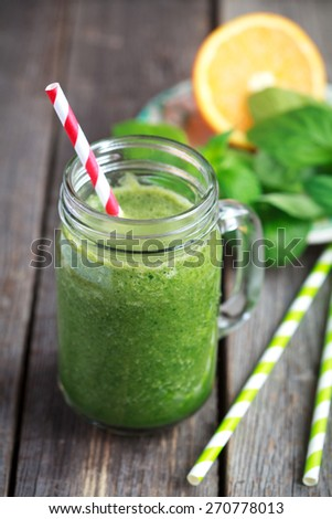 Healthy green smoothie made from spinach, kiwi, bananas and oranges in a jar with red straw on a wooden table, selective focus - stock photo