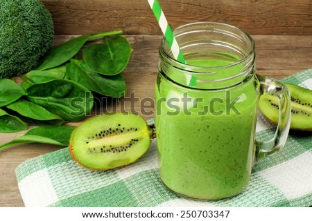 Healthy green smoothie with spinach and kiwi in a jar mug with checkered cloth against wood - stock photo