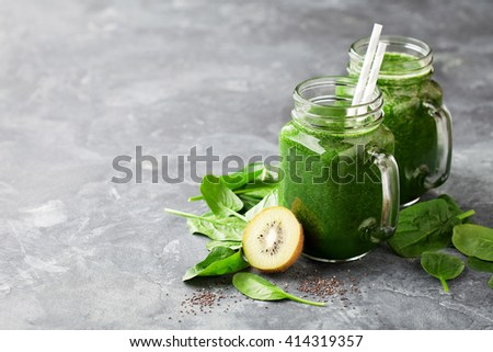 Healthy green smoothie with spinach, kiwi and chia seeds in a jar mug, selective focus - stock photo