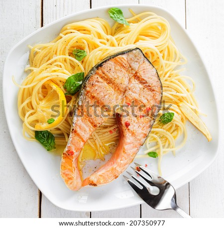 Healthy grilled salmon steak rich in omega-3 fatty acids served on linguine pasta topped with fresh basil , overhead view - stock photo