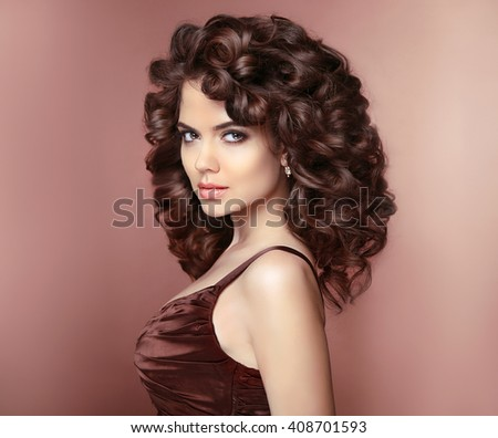 Healthy hair. Beautiful young smiling woman with long curly hairstyle. Brunette with professional makeup. Elegant lady studio portrait.  - stock photo