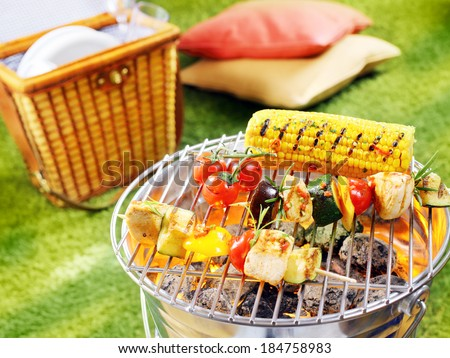 Healthy halloumi kebabs grilling over a fire in a portable barbecue with tomatoes and fresh corn on the cob on a summer picnic in the garden - stock photo