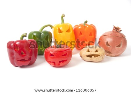 Healthy Halloween faces carved into vegetables such as potato, tomato, paprika, onion and capsicum instead of pumpkin forming special jack o lanterns. - stock photo