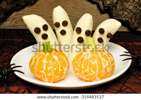Healthy Halloween treats, banana ghosts and orange pumpkins, on a plate with holiday decor - stock photo