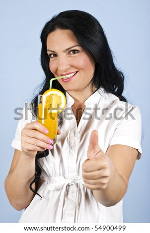 Healthy happy brunette woman giving thumbs up and holding a glass of fresh orange juice in hand,looking and smiling you dressed in white clothes on blue background - stock photo
