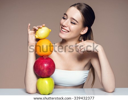 Healthy & Happy, natural organic raw fresh mix fruits concept / portrait of girl with fruits mix on the table over beige backdrop - stock photo