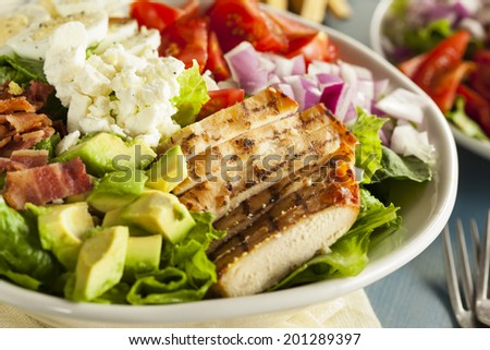 Healthy Hearty Cobb Salad with Chicken Bacon Tomato Onions and Eggs - stock photo
