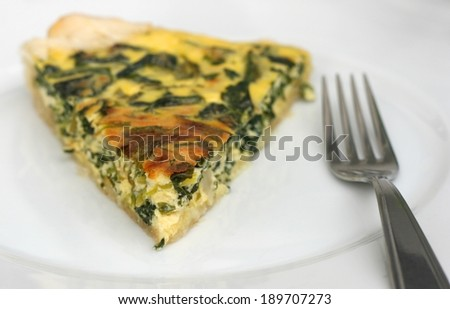Healthy home made vegetarian meal - piece of quiche or pie with spinach, eggs and low fat sour cream and mozzarella - stock photo