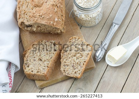 Healthy homemade bread with oatmeal on a rustic wooden table. Up view. - stock photo