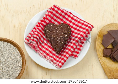 Healthy homemade dark chocolate chia seed gluten free love heart cookie with ingredients - stock photo