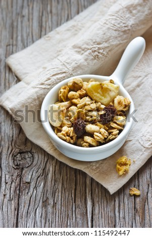Healthy homemade granola cereal on an old wooden board. - stock photo