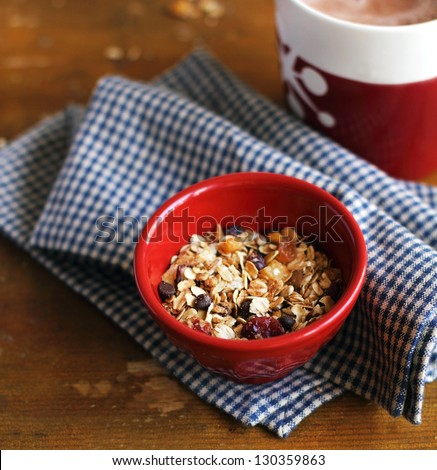 Healthy homemade granola or muesli with oats, dried pears, raisin, almonds, hazelnuts and honey in a red bowl for breakfast - stock photo